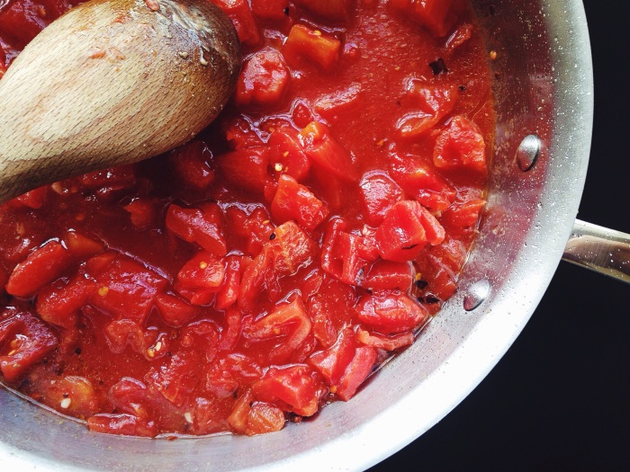 I like to crush about half the pan of tomatoes with the back of a wooden spoon to make it saucier